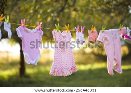 Pink baby wear outdoor in garden - stock photo