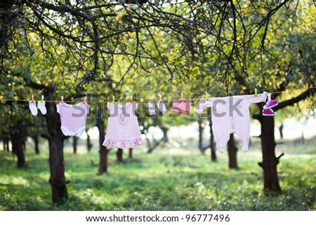 Pink baby wear outdoor in garden - stock photo