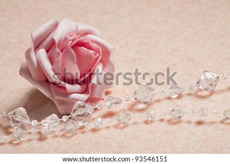Pink background with rose and  beads - stock photo