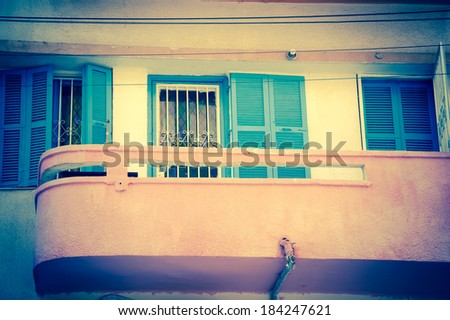 Pink balcony and the windows with colorful stained glass and  turquoise shutters. Old building with stucco wall. Bauhaus architectural style. Tel Aviv, Israel. Aged photo.  - stock photo