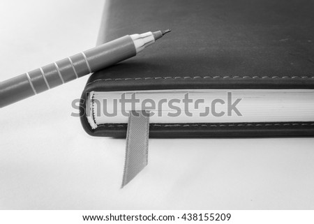 Pink ball pen on closed notebook, selective focus (black and white effect) - stock photo