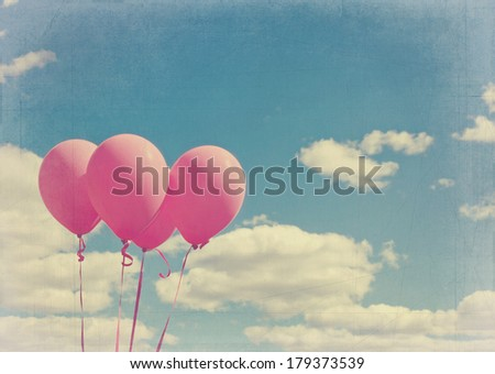 Pink balloons on blue sky with vintage editing and texturing - stock photo