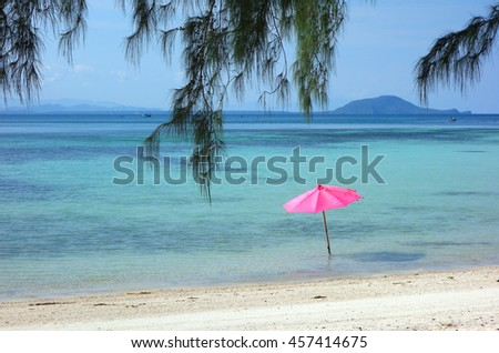 Pink beach umbrella on the sandy beach on summer day.  - stock photo