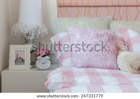 pink bedroom with pink pillows on bed and white alarm clock on table at home - stock photo