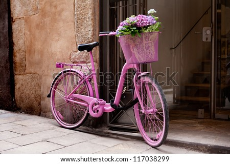 pink bicycle standing on the street - some flowers in the basket - stock photo