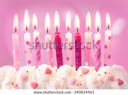 Pink birthday candles and balloons - stock photo