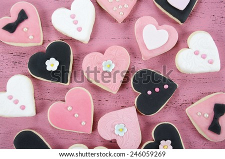 Pink, black and white homemade heart shape cookies on vintage shabby chic pink wood background for Valentines Day, wedding, Mothers Day or female birthday, overhead. - stock photo