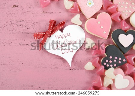 Pink, black and white homemade heart shape cookies on vintage shabby chic pink wood background with Happy Valentines Day greeting gift tag and sample text. - stock photo