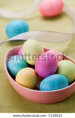 Pink bowl of pastel Easter eggs with ribbon