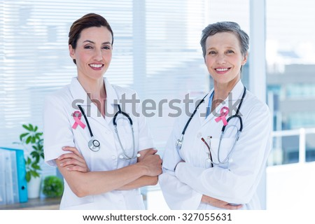 Pink breast cancer awareness ribbon against portrait of smiling medical colleagues with arms crossed - stock photo