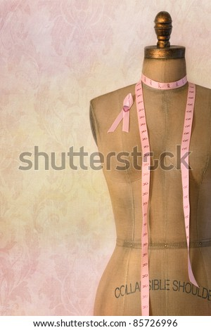 Pink breast cancer ribbon on mannequin  dress form with vintage background - stock photo