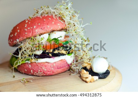 Pink burger with quail eggs and sprouted lentils. Served on a wooden board with walnuts.