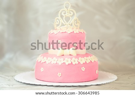 Pink cake with a crown in a white plate over a white tablecloth - stock photo