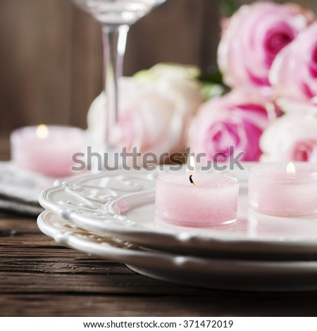 Pink candle and roses on the table, selective focus and square image