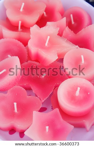 Pink candles, shaped as flowers, stars, leaves and round, on display on a candle stall.