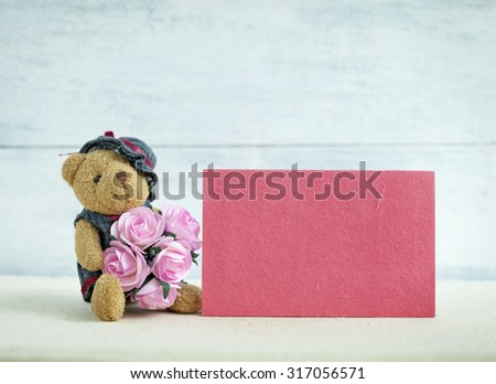 Pink card and Teddy bear holding pink paper rose flowers - stock photo