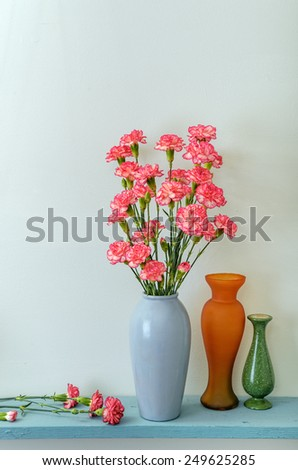 Pink Carnations Being Arranged in Vase - stock photo