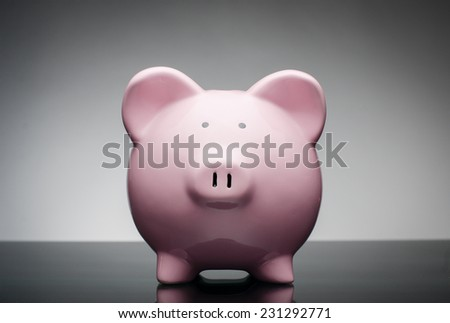 Pink ceramic piggy bank standing facing the camera against a grey background with corner vignette in a financial and savings concept
