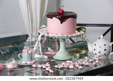 Pink Cherry Cake Topped with Chocolate Ganache on Cake Stand Surrounded by Peppermint Candies on Glass Table with Polka Dot Tea Pot - stock photo