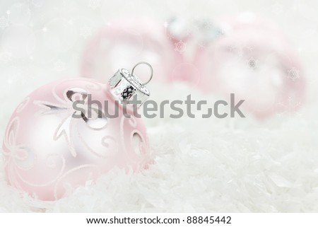 Pink Christmas baubles lying in the snow. Shallow depth of field. - stock photo