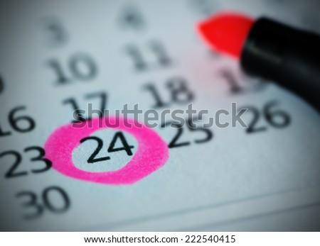 Pink circle. Mark on the calendar at 24. - stock photo