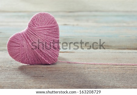 Pink clew in shape of heart on vintage wooden background - stock photo