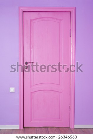 Pink closed door on violet wall - stock photo