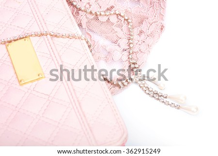 Pink clutch and jewelry with crystals on a white background - stock photo