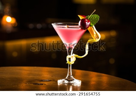 Pink cocktail with cherry and mango in a club. - stock photo