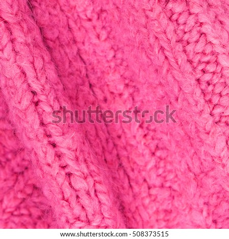 Pink color texture of knitted woolen fabric for wallpaper. Colorful sweater abstract background