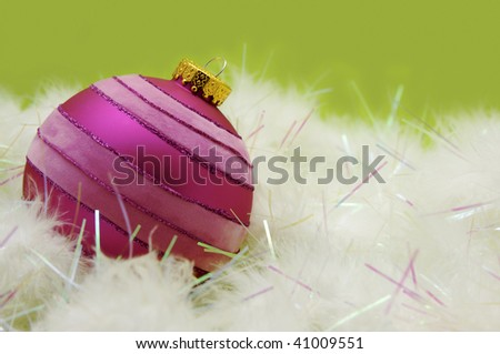 Pink colored Christmas tree ornament surrounded by white fur tinsel against a light green background.