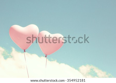 Pink coral heart balloons over a pastel blue sky - stock photo