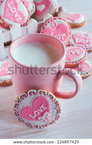 pink cup with milk and homemade cookies with frosting - stock photo