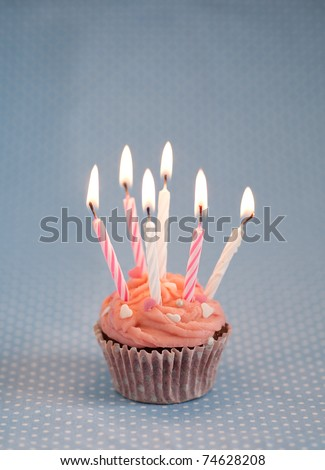 Pink cupcake with candles - stock photo