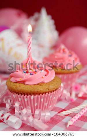 Pink cupcake with candles, birthday hats and ballounes in background - stock photo
