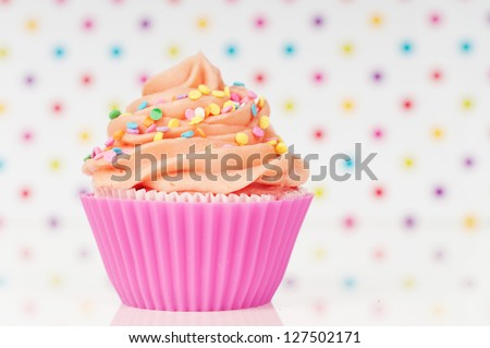 Pink cupcake with whipped cream and sprinkles on a rainbow dotted background