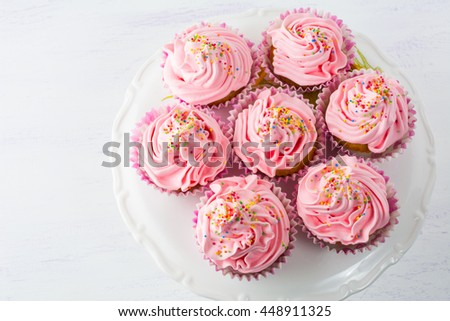 Pink cupcakes  on cake stand top view. Birthday cupcake with whipped cream. Homemade cupcakes served for party. Birthday background. - stock photo