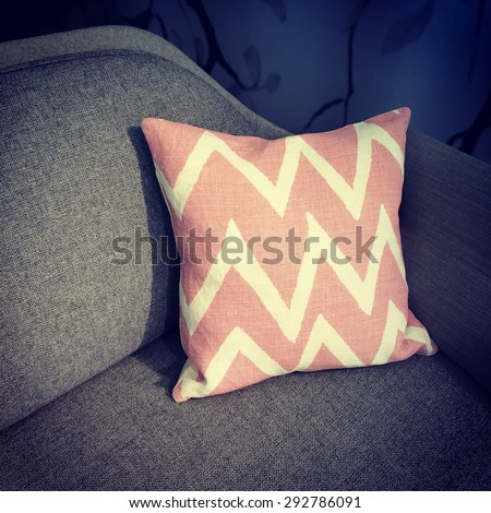 Pink cushion with modern design decorating a sofa. - stock photo