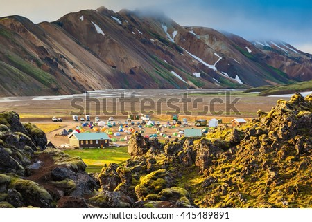 Pink dawn in the Iceland. Striped mountains of rhyolite covered the warm sunshine. In valley of the park is located tourist camping