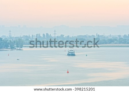 Pink daybreak over blue the river and the city skyline in the haze on the horizon - stock photo