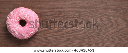 Pink donut on wooden background, top view. Space for text