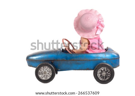 pink dressed Little girl driving big vintage old toy car and having fun - stock photo