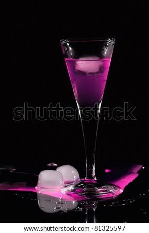 Pink drink with ice cube in darkness - stock photo
