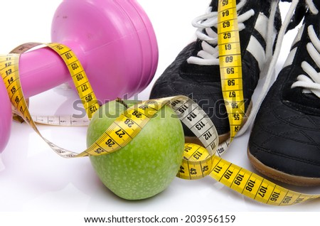 Pink dumbbell, an apple and fitness shoes with a tape measure, isolated on white - stock photo