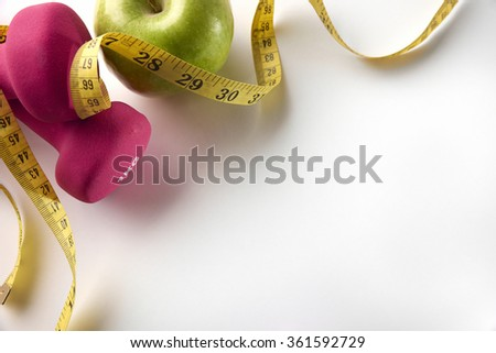 Pink dumbbells with apple and tape measure. Concept health, diet and sports. Horizontal composition. Top diagonal view - stock photo