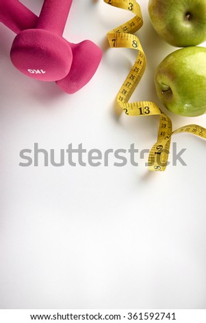 Pink dumbbells with apple and tape measure. Concept health, diet and sports. Vertical composition. Top view - stock photo