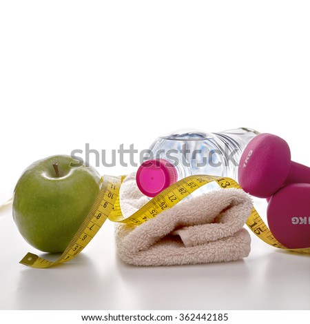 Pink dumbbells with apple, mineral water bottle, towel and tape measure on white table and isolated background. Concept health, diet and sports. Square composition. Front view - stock photo