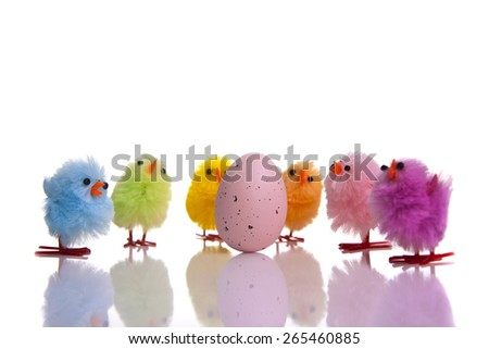 Pink Easter egg surrounded with colourful chicks isolated on white background with reflection - stock photo