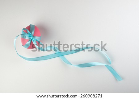 pink easter egg with a blue bow isolated on white background - stock photo