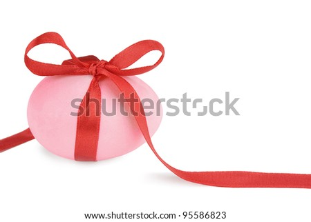 Pink Easter egg with a red ribbon isolated on white background